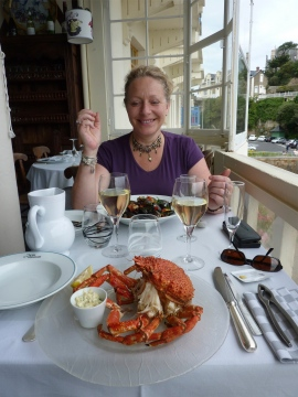 Gabrielle sat at a restaurant table with a cooked spider crab on a plate and a glass of wine